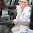 Young woman assistant old lady out of care — 图库照片