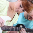 Teenagers with guitar indoors — Stock Photo