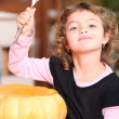 Stock Photo: Young girl carving a pumpkin
