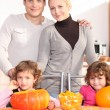 Family gathered around kitchen table preparing pumpkins — ストック写真