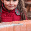 Little girl stood by brick wall — Stock Photo #7623963