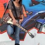 A female guitarist standing before a graffiti. — Stock Photo
