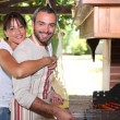 Smiling couple preparing barbecue — Stock Photo