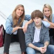 Three teenage friends sat on steps — Stock fotografie #7624407