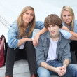 Foto Stock: Three teenage friends sat on steps
