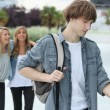 Three teenagers arriving at college - Stock Photo