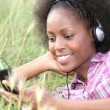 Stock Photo: Womlistening to music in field of grass