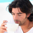 Man drinking coffee by swimming pool — Stock Photo #7624508