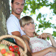 Couple sat by tree with basket of fresh produce — Stock Photo #7624718