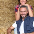 Farmer couple sitting amongst hay bales - Stock Photo