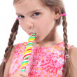 Girl sucking on candy stick — Zdjęcie stockowe #7624861