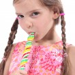 Girl sucking on candy stick — стоковое фото #7624861