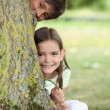 Two little children hiding behind tree - Stock Photo