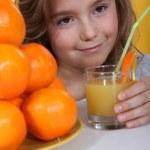 A little blonde girl drinking orange juice — Stock Photo