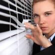 Woman looking through venetian blinds - Stockfoto