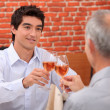 Young man and senior chinking wine glasses - Stock Photo
