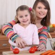 Mother and daughter slicing tomatoes - Stock Photo