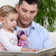 Man and little girl reading a book — Stock Photo
