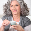 Mature woman having cup of coffee home — Stock Photo