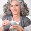 Mature woman having cup of coffee home — Stock Photo #7625578
