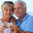 Mature couple looking at the photos on their digital camera — Stock Photo #7625718