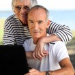 Foto Stock: Elderly couple with computer