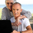 Elderly couple with a computer — Stock Photo