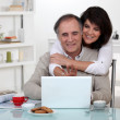 Couple smiling in front of their laptop — Stock Photo