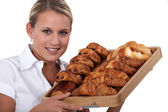 Blonde woman holding a platter of croissants — Stock Photo