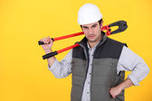 Tradesman carrying a pair of large clippers on his shoulder — Stock Photo
