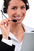 Cheerful, smiling woman with a headset and laptop — Stock Photo
