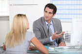 Suited man talking to a young woman across a desk — Stock Photo