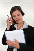 Woman adjusting her headset and holding a clipboard — Stock Photo