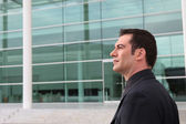 Businessman outside a glass fronted building — Stock Photo