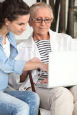 Young woman helping an elderly lady navigate the internet — Stock Photo