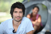 Young man camping with his girlfriend and tent out of focus in the backgrou — Stock Photo