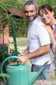 Couple filling up watering can — Stock Photo