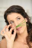 Woman smellinggrass — Stock Photo