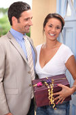 A beautiful woman received a gift from a well dressed man — Stock Photo