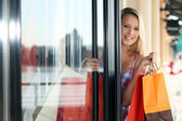 Blond woman coming out of clothes shop — Stock Photo