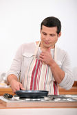 Young man in apron cooking — Stock Photo