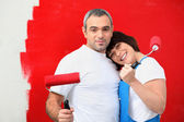 Couple painting wall red — Stock Photo