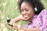 Woman listening to music in a field of grass — Stock Photo
