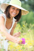 Woman picking flowers in field — Stock Photo