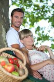 Couple sat by tree with basket of fresh produce — Stock Photo