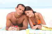 Couple laying on towel at the beach — Stock Photo
