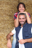 Farmer couple sitting amongst hay bales — Stock Photo