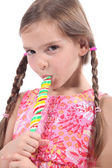 Girl sucking on a candy stick — Stock Photo