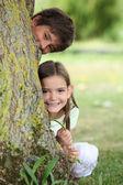 Dvě malé děti, schovává se za strom — Stock fotografie