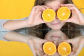 Girl with orange halves in front of her eyes — Stock Photo